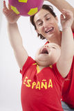 Family spanish soccer fans playing. Blonde baby sixteen month old and mother with red shirt of Spanish soccer team with ball Royalty Free Stock Image