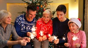 Family with sparklers at Christmas time. At home Royalty Free Stock Photos