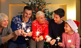 Family with sparklers at Christmas time. At home royalty free stock photo