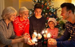 Family with sparklers at Christmas time. At home stock photo