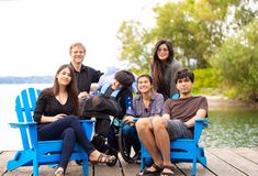 Family with special needs child sitting outdoors together in sum. Multiracial family with special needs child sitting outdoors together on summer day. Child is royalty free stock image