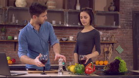 Family spend day off in flat. Happy couple cooking dinner on the kitchen. Young people cook salad drinking wine toasting enjoy evening talking. Beautiful couple stock footage