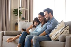 Family spend free time watching cartoons on mobile phone. Married diverse couple spend free time on weekend with small daughter sitting on sofa in living room at royalty free stock photos