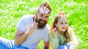 Family spend leisure outdoors, play girlish games. Child and father posing with crown and bow photo booth attributes. Fatherhood concept. Dad and daughter sits royalty free stock images