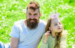 Family spend leisure outdoors, play girlish games. Dad and daughter sits on grass at grassplot, green background. Child. And father posing with crown and bow stock photography