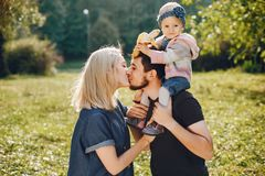 Family spend time in a park. Cute family in a park. Beautyful mother with her little daughter. Man in a black t-shirt stock photo