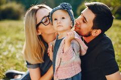 Family spend time in a park. Cute family in a park. Beautyful mother with her little daughter. Man in a black t-shirt stock image