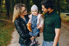 Family spend time in a park. Cute family in a park. Beautyful mother with her little daughter. Man in a green t-shirt stock images