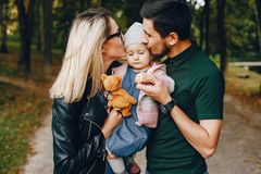 Family spend time in a park. Cute family in a park. Beautyful mother with her little daughter. Man in a green t-shirt royalty free stock photography