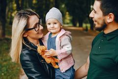 Family spend time in a park. Cute family in a park. Beautyful mother with her little daughter. Man in a green t-shirt royalty free stock photo