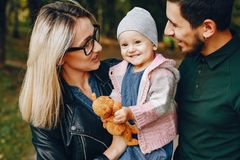 Family spend time in a park. Cute family in a park. Beautyful mother with her little daughter. Man in a green t-shirt royalty free stock photos