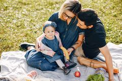 Family spend time in a park. Cute family in a park. Beautyful mother with her little daughter. Woman in a glasses. Picnic in a garden royalty free stock photos