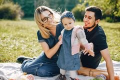 Family spend time in a park. Cute family in a park. Beautyful mother with her little daughter. Woman in a glasses. Picnic in a garden royalty free stock image