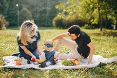Family spend time in a park. Cute family in a park. Beautyful mother with her little daughter. Woman in a glasses. Picnic in a garden stock photo