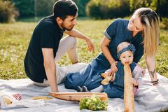 Family spend time in a park. Cute family in a park. Beautyful mother with her little daughter. Woman in a glasses. Picnic in a garden royalty free stock photography