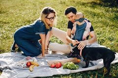 Family spend time in a park. Cute family in a park. Beautyful mother with her little daughter. Woman in a glasses. Picnic in a garden royalty free stock photo