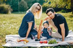 Family spend time in a park. Cute family in a park. Beautyful mother with her little daughter. Woman in a glasses. Picnic in a garden stock photography