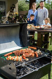 Family spend time together at barbecue. Selective focus of meat and vegetables cooking on grill Stock Photo