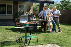 Family spend time together while having barbecue with grill at yard Royalty Free Stock Photos
