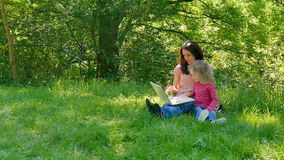 Family Spend Time Together Outdoors Using White Laptop. Two Girls are Playing Video Games Sitting on the Green Grass in. The City Park, HD stock video