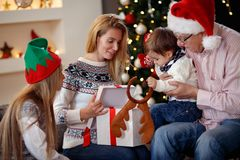 Family spending Christmas time opening the gifts. Happy family spending Christmas time opening the gifts stock images