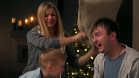 Family spending free time at home. Cheerful family having fun with their son on the bed. On the eve of Christmas and New. Family spending free time at home stock footage