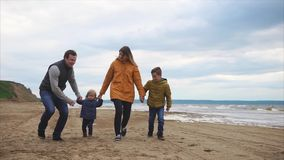 Family spending leisure time together outdoor. Slow motion steadicam shot of a happy family with two children having enjoyable walk at the sea beach on chilly stock footage