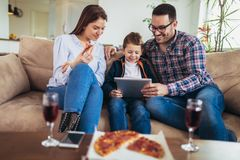 Family spending time at home and looking something fanny on tablet. Happy family spending time at home and looking something fanny on tablet stock photos