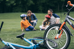 Family spending time at park, selective focus on bicycles at foreground. Happy family spending time at park, selective focus on bicycles at foreground Royalty Free Stock Image