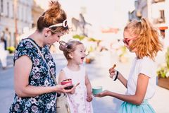 Family spending time together in the city centre enjoy eating ice cream on a summer day Stock Photo
