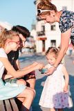 Family spending time together in the city centre enjoy eating ice cream on a summer day Stock Images