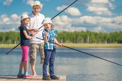 The family spends time on fishing, people on the pier. Near the lake Stock Image