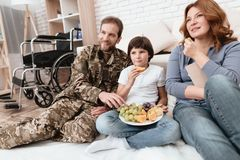 The family spends time together. A disabled father in military uniform is eating fruits with his family. They are watching a tv Royalty Free Stock Photos
