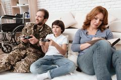 The family spends time together. A disabled father in military uniform is playing with his son on console. Mother is reading a book near them Stock Image
