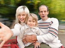 Family on spinning roundabout Stock Photos