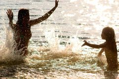 Family splashes in water. The silhouette family gaily splashes in water, outdoor, evening or morning Stock Image