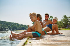 Family splashing water with their feet Royalty Free Stock Image