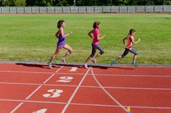 Family sport and fitness, happy mother and kids running on stadium track outdoors, children healthy active lifestyle. Concept royalty free stock image