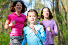 Family sport, happy active mother and kids jogging outdoors. Running in forest Stock Photo