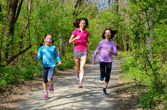 Family sport, happy active mother and kids jogging outdoors. Running in forest stock photos