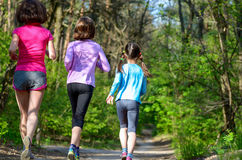 Family sport, happy active mother and kids jogging outdoors. Running in forest Royalty Free Stock Photo