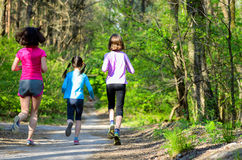 Family sport, happy active mother and kids jogging outdoors. Running in forest royalty free stock image