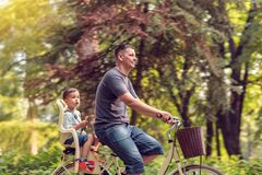 Family sport and healthy lifestyle. Father and son riding bike i Stock Images