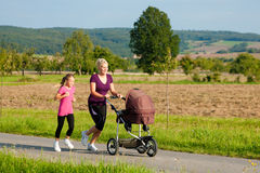 Family sport - jogging with baby stroller Stock Photo