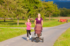 Family sport - jogging with baby stroller. Family sport - mother and daughter jogging down a path with a baby stroller at a wonderful sunny day Royalty Free Stock Photo