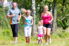 Family sport jogging through field. Parents with children sport running together through forest Royalty Free Stock Images