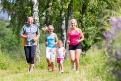Family sport jogging through field. Parents with children sport running together through forest Stock Photo