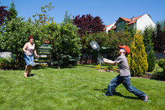 Family sport - playing badminton. Young boy and mature woman playing badminton in garden Royalty Free Stock Photo