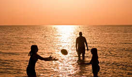 Family Sports at the Beach. A family enjoys football in the ocean as the sun sets stock photos