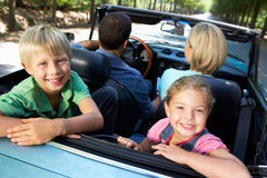 Family in sports car. With children smiling at camera royalty free stock images
